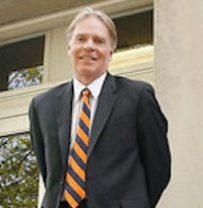 Andrew Greeley outside in suit