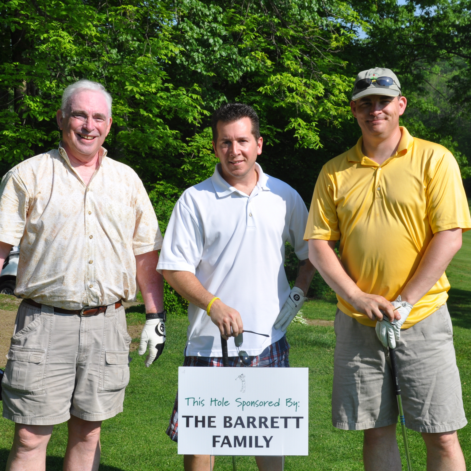 The Barrett family holding a sign that they sponsored a hole in a golf course